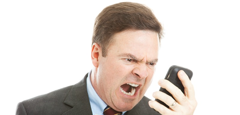 Angry businessman yelling into a cellphone.